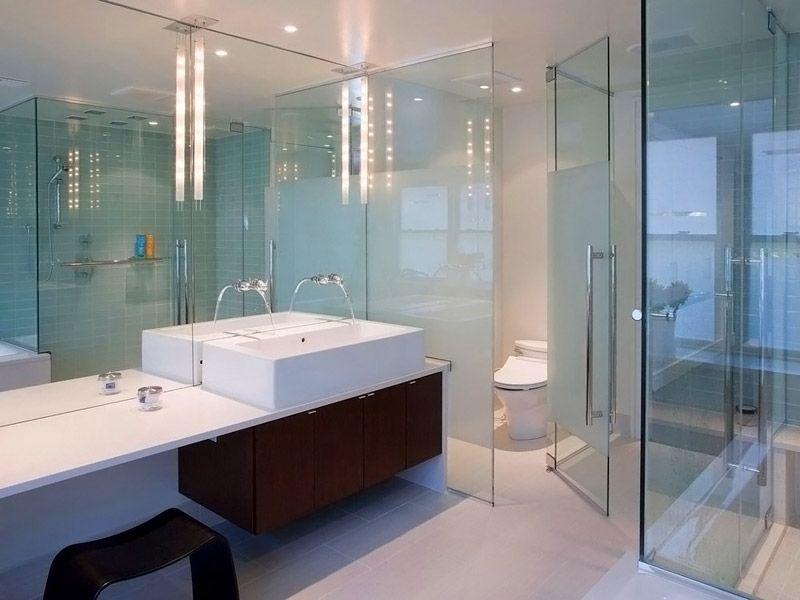 В этом дизайне ванной комнаты облицовка плиткой выполняет функции фона. Основные акценты сделаны с помощью перегородок, зеркал и оригинальной мебели