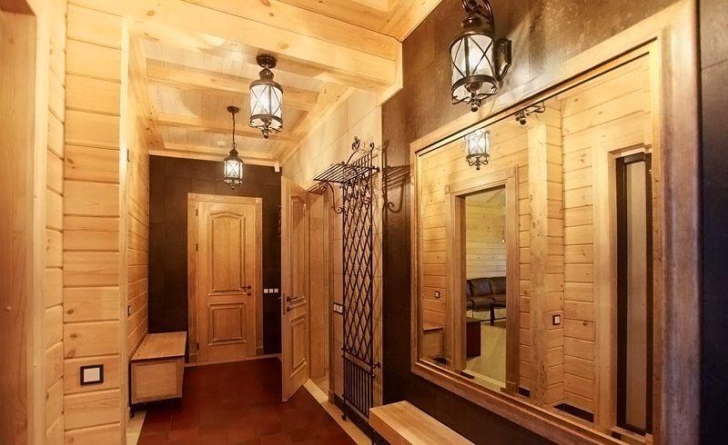 Люстры должны соответствовать общей стилистике прихожей. На этом фото стилизованные фонари очень удачно вписались в интерьер деревянного дома