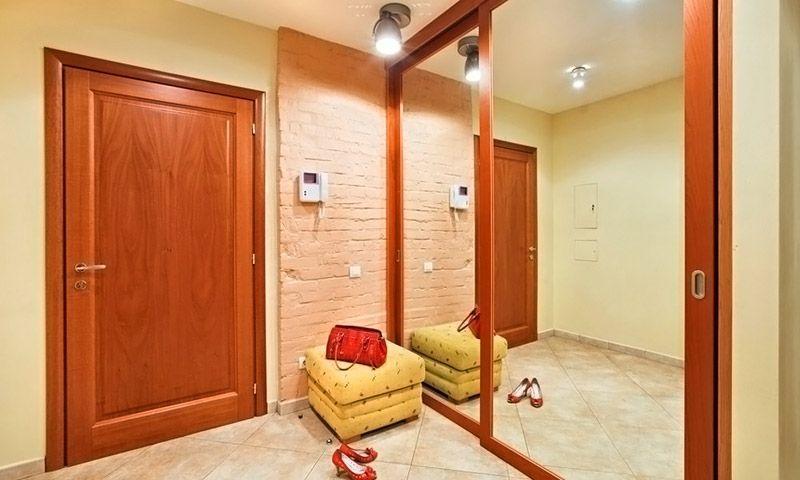 За счёт удачно расположенных светильников и большого зеркала в маленькой прихожей стало больше места