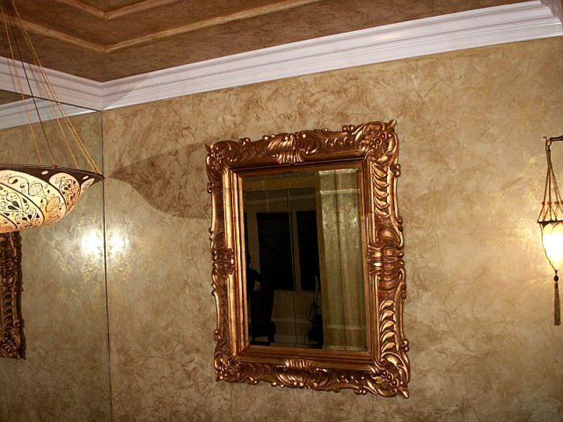 На «мраморной» поверхности уместно выглядит зеркало в багетной раме