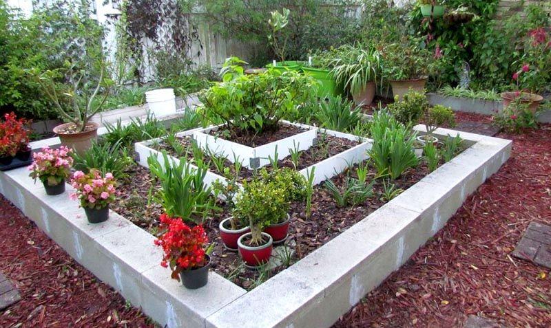 Многоярусное сооружение из разных материалов. На широкие ограждения можно поставить дополнительные емкости с растениями