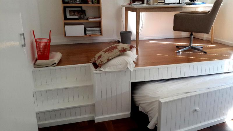 Отличная идея для размещения спальни – подиум. В нем можно скрыть выдвижные ящики для хранения белья или даже саму кровать