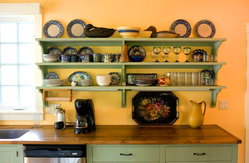 Навесные полки на кухне используют как место для хранения с элементами декора
