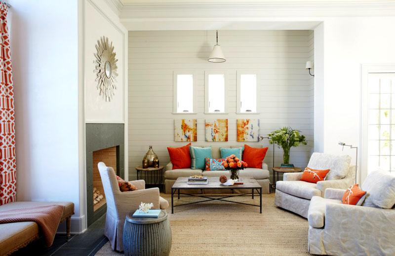 Прохладный белый интерьер гостиной можно разбавить яркими диванными подушками