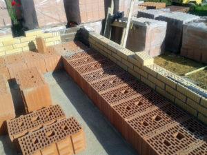 Процесс кладки стен с помощью поризованного кирпича. Улучшенное «сцепление» осуществляется за счёт специальных неровных краев с пазами