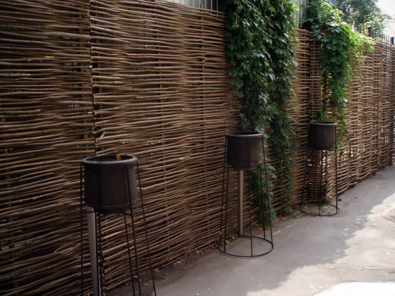 Забор из орешника и лещины достаточно плотный, чтобы скрыть неприглядные постройки от посторонних глаз. Чаще всего ими огораживают участки сада, где находятся зона отдыха или шезлонги