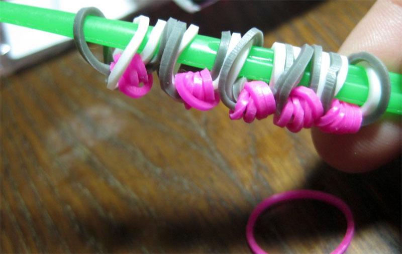 Взять фиолетовую резинку, протянуть её через все детали и завязать узелком