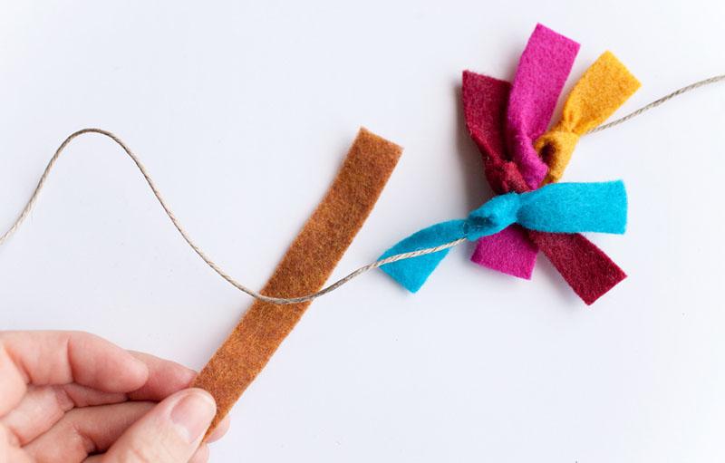 На верёвке завязать узелками полоски из фетра. Чем больше деталей будет, тем интереснее получится гирлянда