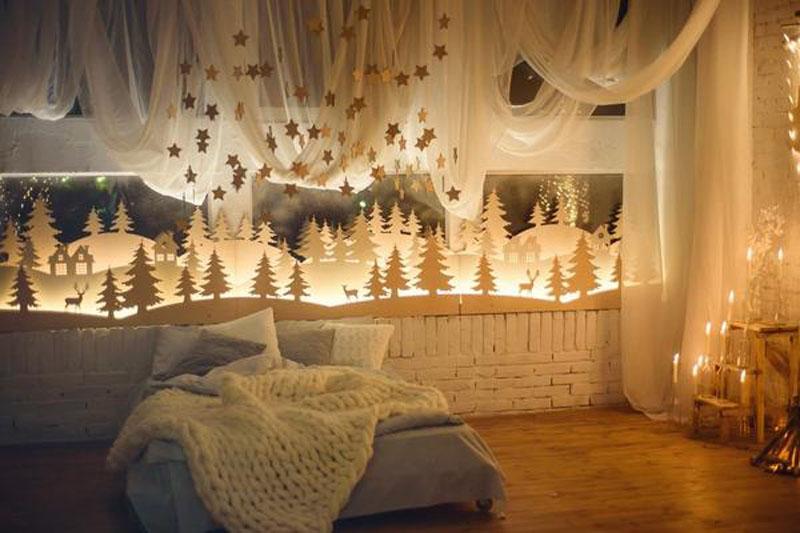 Из ватмана можно вырезать зимний лес. Если сделать несколько ярусов и проложить между ними светящиеся гирлянды, подоконник в вечернее время озарит комнату особенным таинственным светом