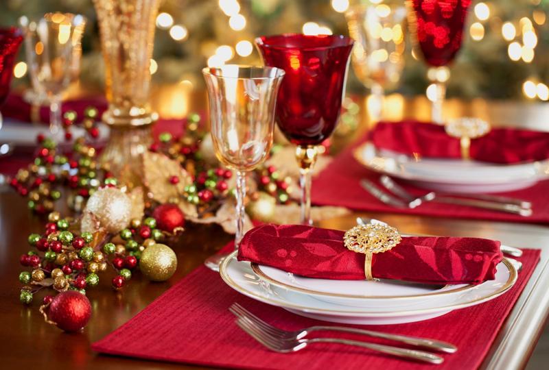 Между посудой размещают ёлочные украшения, гармонирующие с общим цветовым фоном стола