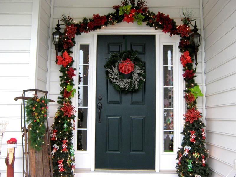 Крыльцо и двери традиционно оформляют с помощью хвойных и светодиодных гирлянд и венков