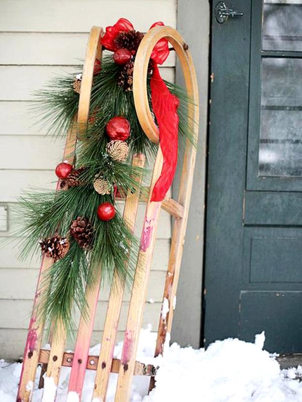 Если в доме есть новогодние саночки, это прекрасно. На них вешают связку из веток хвои, колокольчики и ленты