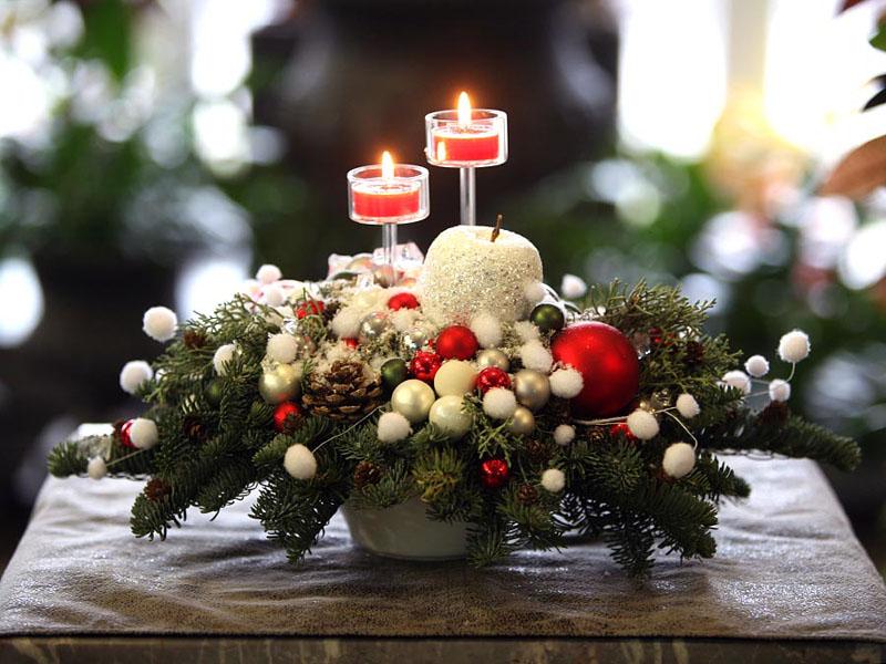 Еловые ветви могут помочь в украшении стола в гостиной. На них замечательно располагаются игрушки и шишки, а искусственный снег сделает композицию зимней и прелестной