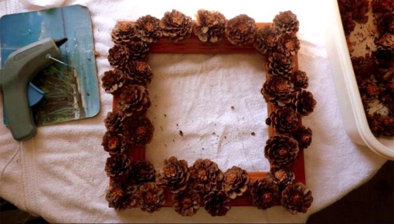 Такая рамка неплохо выглядит сама по себе, но дополнительное декорирование ленточками и красивыми бусинками сделает ее еще прекраснее. Чтобы придать эффект снега, можно нанести клей на чешуйки и присыпать мелкой солью
