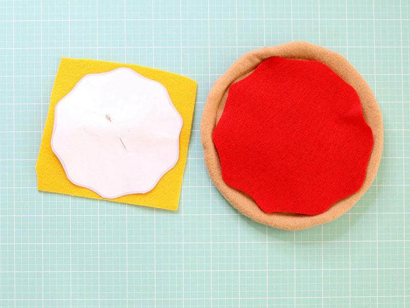 Подготовить основу, внутрь около края вложить наполнитель– это будут бортики, из красного фетра вырезать соус, из желтого – сыр