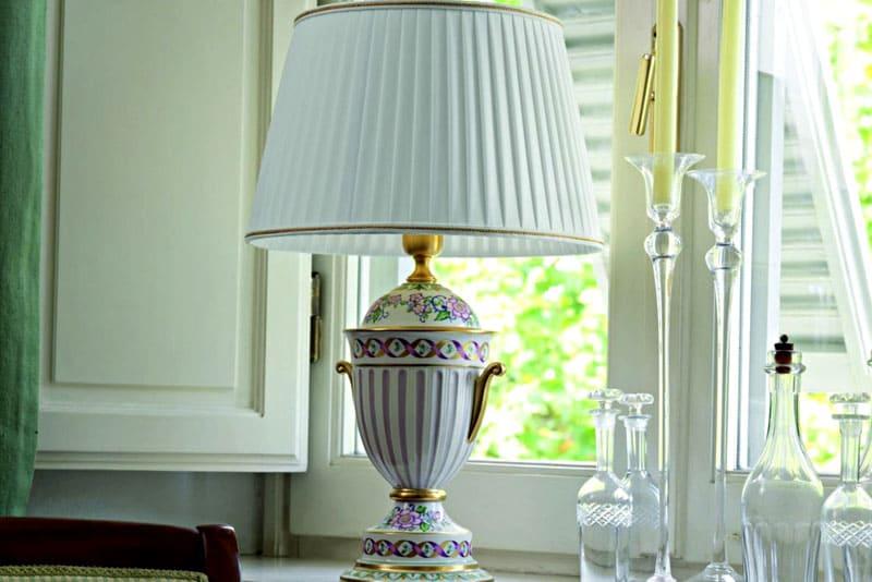 Основной признак такой лампы – роскошный абажур. Он может быть выполнен из ткани с рисунком или украшен бахромой, вышивкой или кружевом в зависимости от выбранного стиля