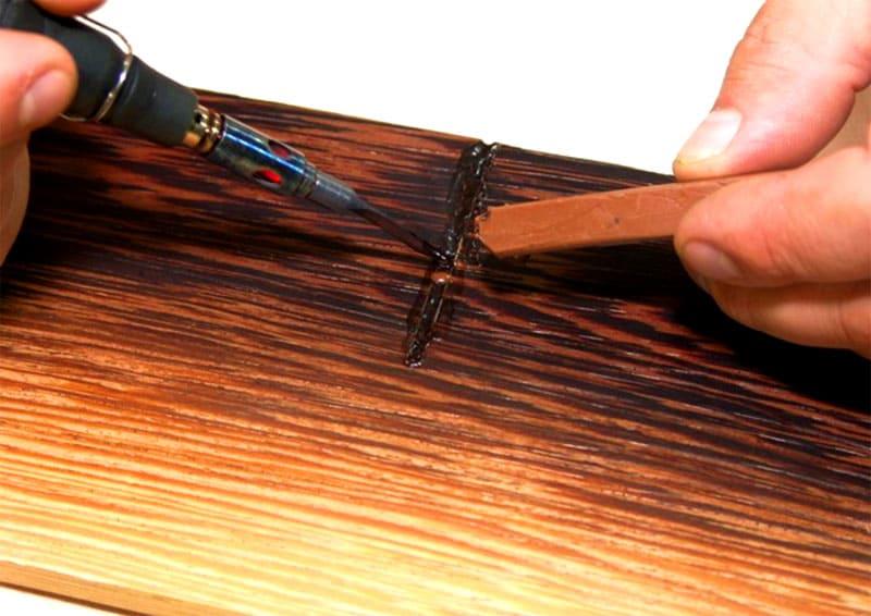 Отреставрировать небольшие трещинки можно подходящим по цвету воском