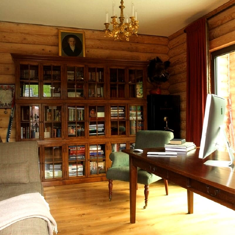 Для книг, сценариев и рабочих документов в кабинете установлен шкаф из дерева со стеклянными фасадами в духе общего стиля дома