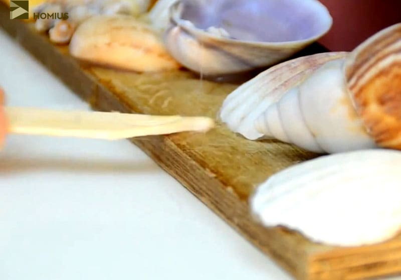 В промежутках обильно наносим клей и начинаем заполнять мелкой галькой или раковинами