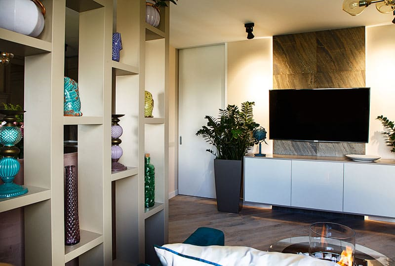Настенная панель за телевизором имитирует бетон с ржавыми прожилками, оттенок которых повторяется в интерьере