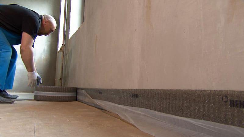 По периметру стен укладывается демпферная лента. Она позволит оставить небольшой зазор, который будет компенсировать температурные расширения состава
