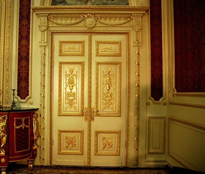 Требования стиля предлагают только двустворчатые двери из натурального массива дуба или бука, контрастного тёмного или белого цвета с изобилием фурнитуры