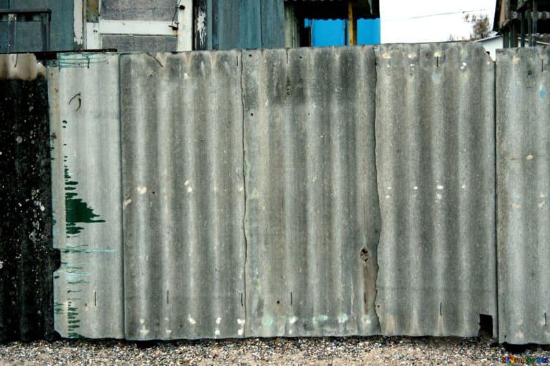 Забор из старого шифера хоть и не слишком эстетичен, зато не требует больших финансовых затрат