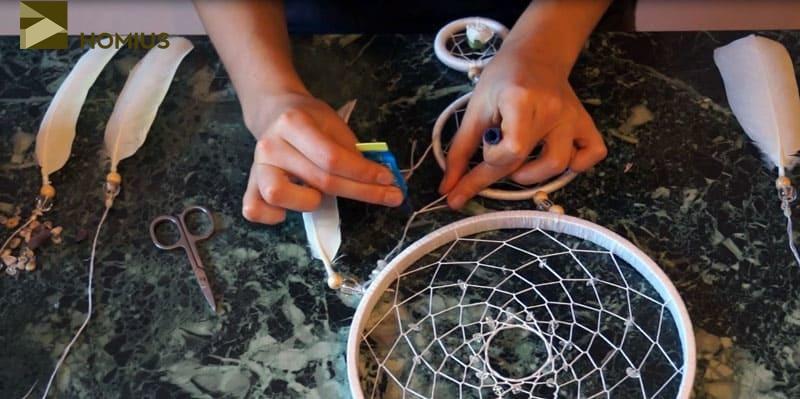 Оставшиеся кончики мы не обрезаем, а надеваем на них бусины, закрепляя внизу петельку, как показано на фото. Далее отрезаем край и у нас получается кисточка