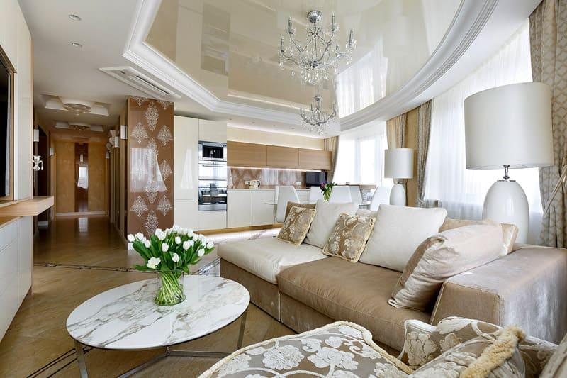 Бежевый глянцевый натяжной потолок гармонирует с мебельной обивкой и фасадами кухонного гарнитура
