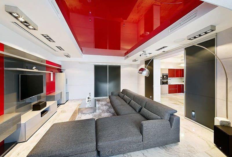Красная глянцевая поверхность многоуровневого потолка создаёт яркий акцент и должна компенсироваться более спокойными цветами в интерьере
