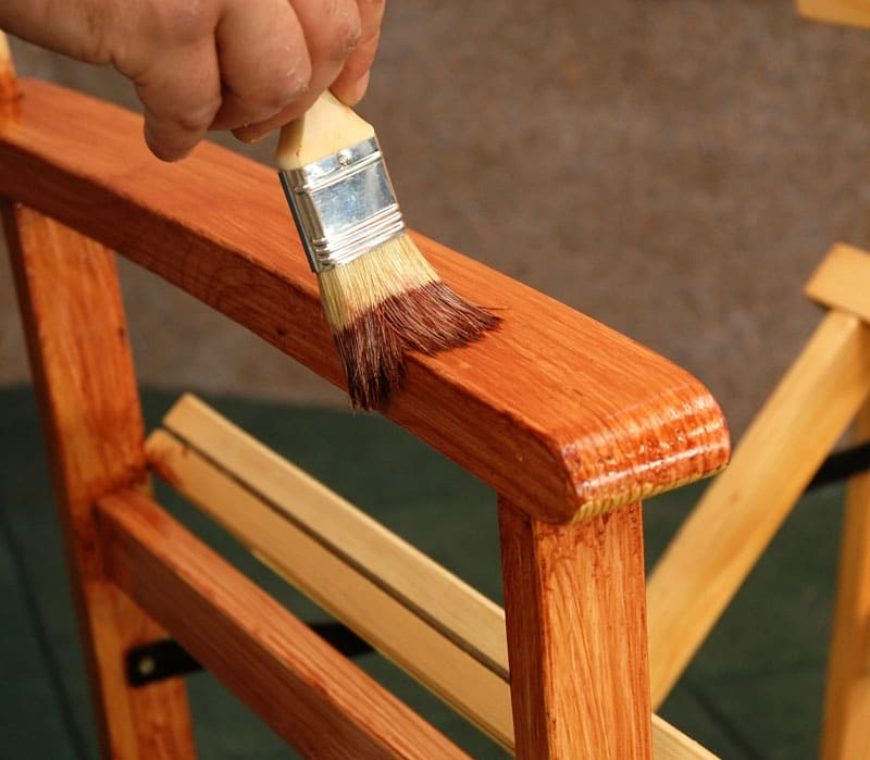 Вырезанные из дерева ножки мастер доводит до окончательной формы и вида, покрывая их специальными пропитками и лаками. Они нужны для того, чтобы защитить дерево от гниения и влаги