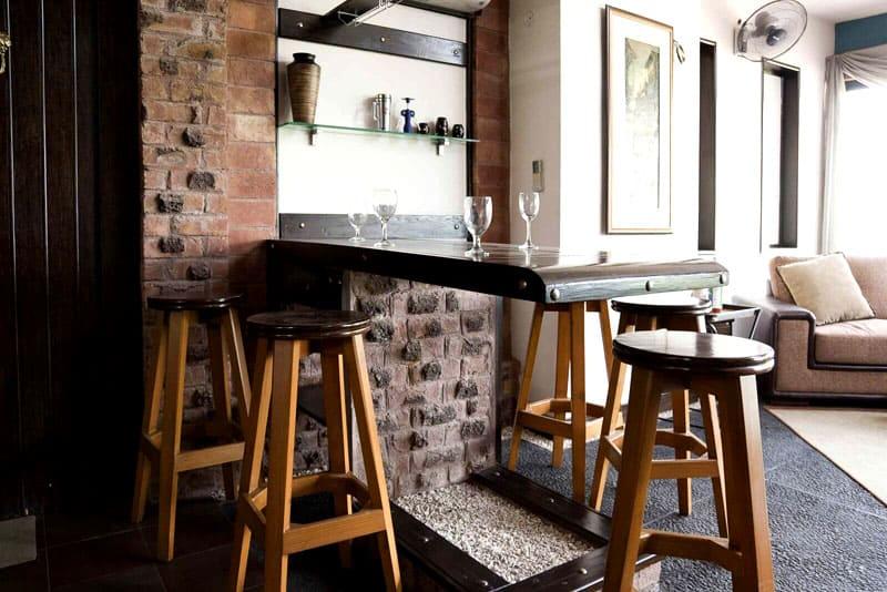Стильная барная стойка из дерева отделяет гостиную от кухонной зоны