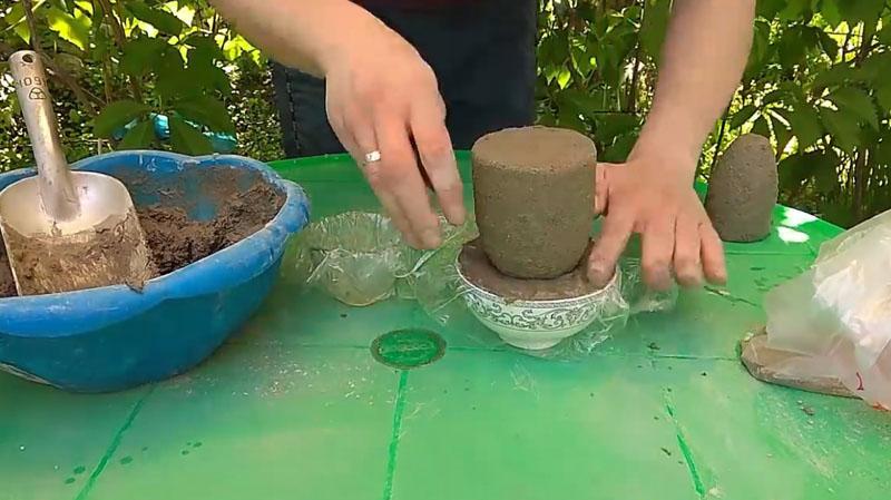 Для этого потребуется неглубокая пиала. По привычной для нас технологии укладываем на её дно обычную клеёнку, далее выкладываем цементную смесь