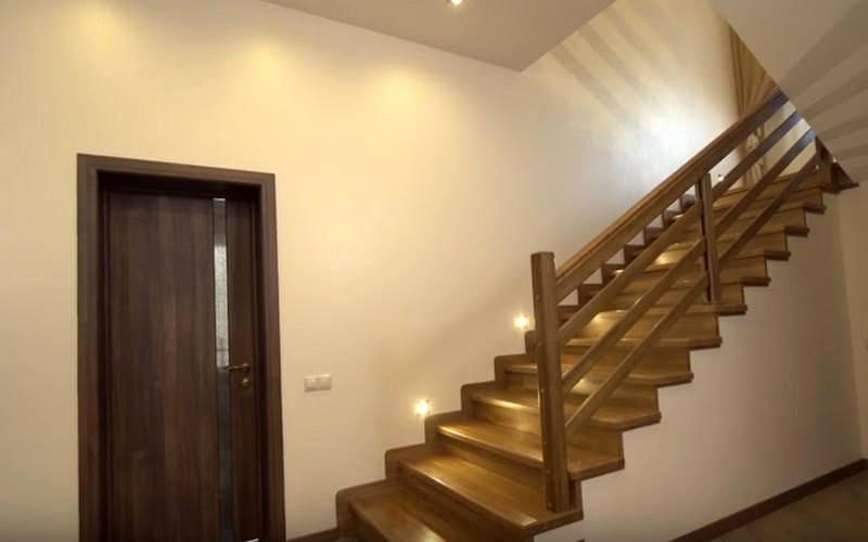 На второй этаж ведет деревянная лестница с точечной подсветкой