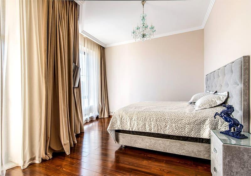 В качестве украшения спальни выступает хрустальная люстра в нежно-голубом оттенке