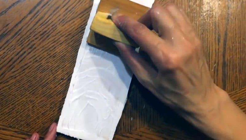 А вот так инструмент показывает себя в работе. Достаточно просто поскользить по поверхности шпаклёвки и немного поводить шпатель, покачивая его
