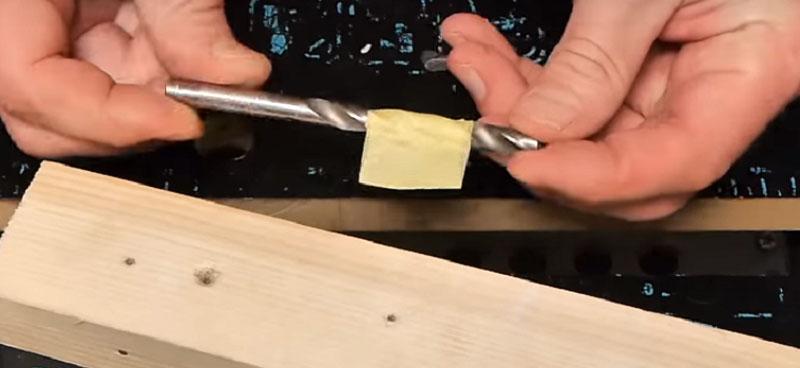 Приложите дюбель к сверлу и зафиксируйте отметку скотчем