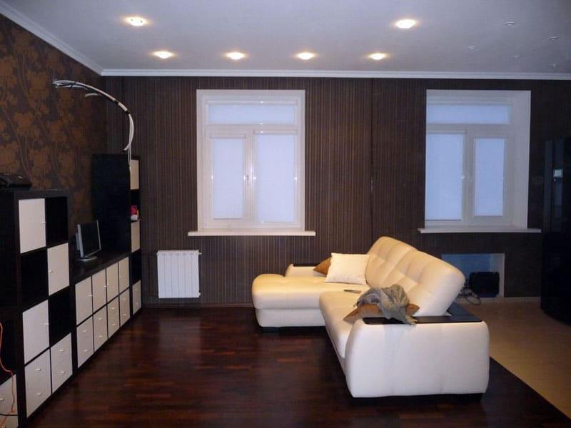 ФОТО: remont-f.ru Тёмное оформление гостиной разбавляет белый диван и модульная стенка с белыми фасадами
