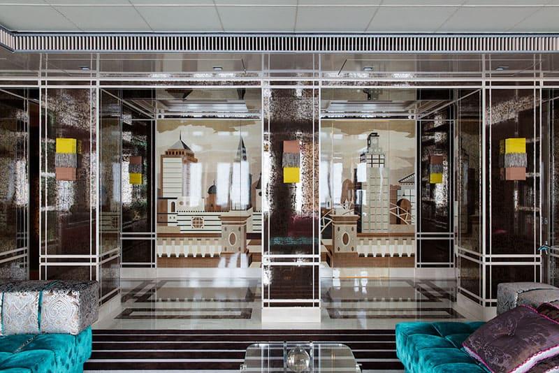 За стеклянным панно с изображением города прячется вход на кухню