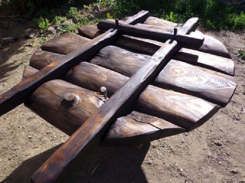 Неплохо смотрятся варианты оформления колодцев, элементы которых изготовлены из натурального необработанного дерева