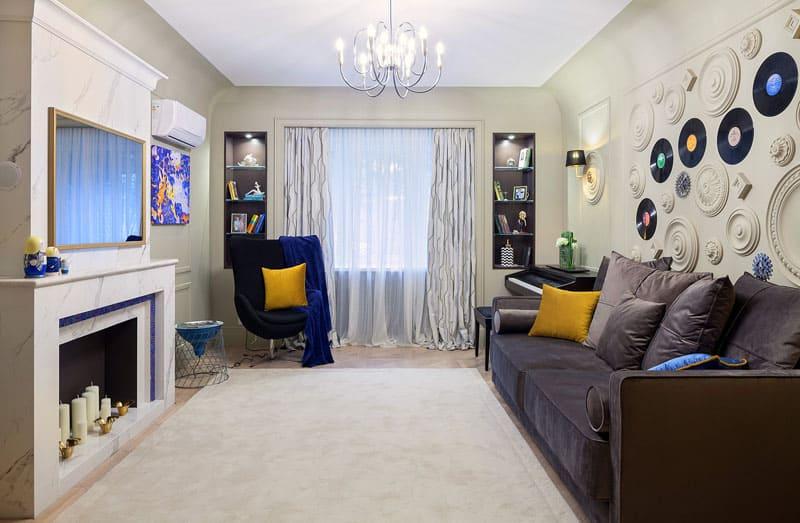 Для декорирования стены в гостиной выбрали неординарное решение – гипсовые накладки и пластинки разных форм и узоров