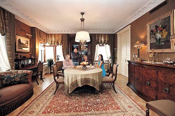 Над обеденным столом в гостиной установили классическую люстру с тканевым абажуром светлого оттенка