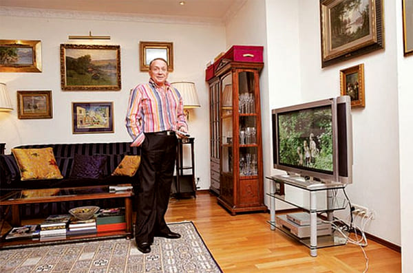 В интерьер не совсем удачно вписывается современный стеклянный столик под телевизор с хромированными ножками