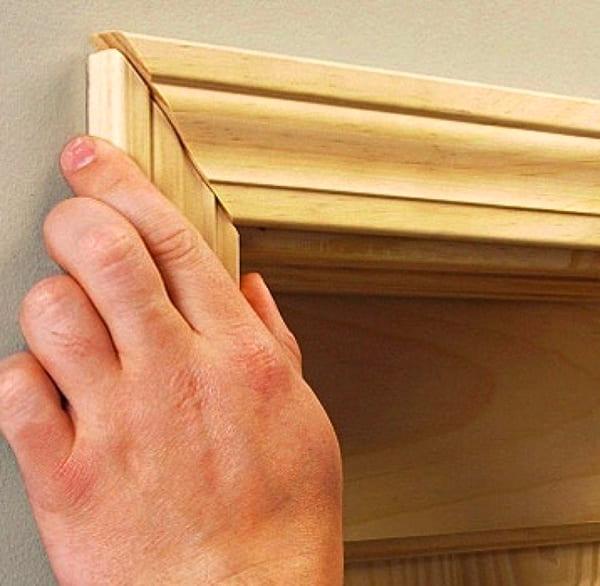 Требуется обезжирить покрытие, на которое приклеивается наличник, на тыльную сторону планки наносится немного клея и прижимается к стене
