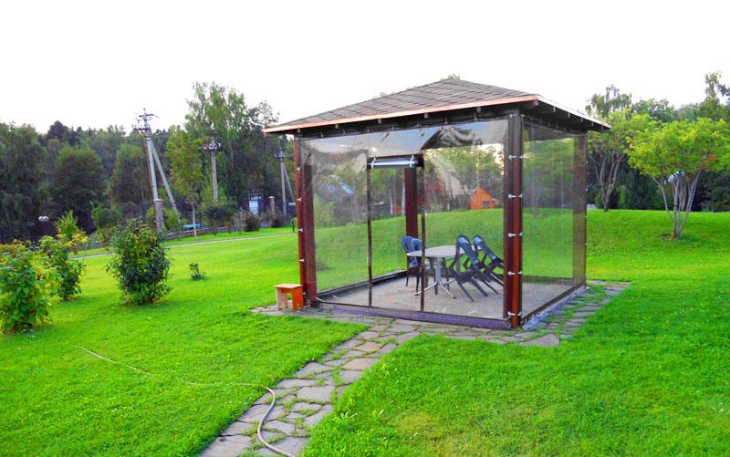 Небольшая квадратная беседка, защищенная шторами ПВХ, используемая в качестве летней столовой для приёма пищи