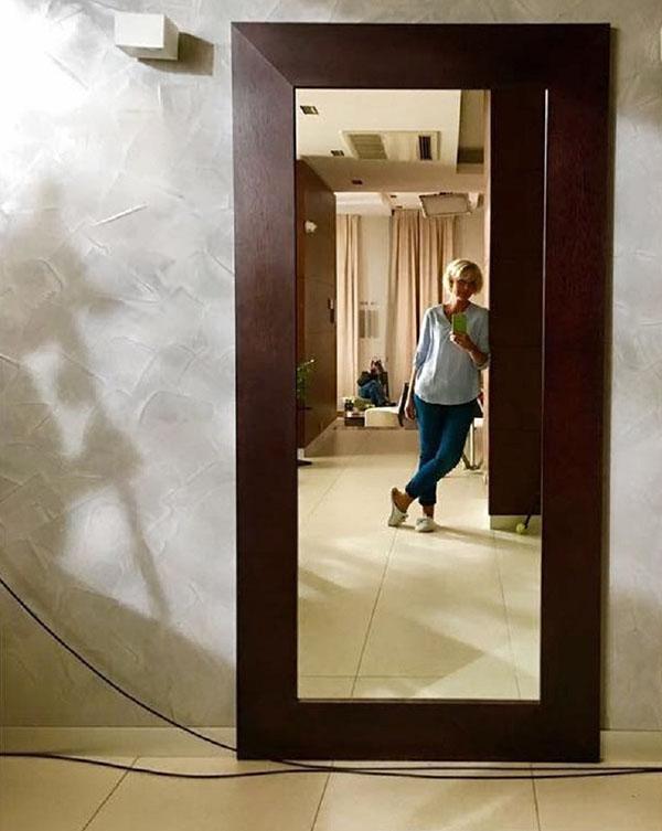 Для коридора выбрали декоративную штукатурку, напоминающую бетон, на фоне которой идеально смотрится зеркало в полный рост в строгой деревянной раме