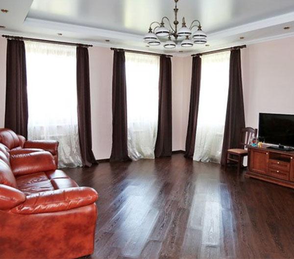Ламинат в гостиной выложен по диагонали, такой приём увеличивает и без того просторное помещение