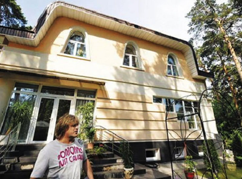 Фасад дома сразу привлекает к себе внимание нестандартными оконными проёмами