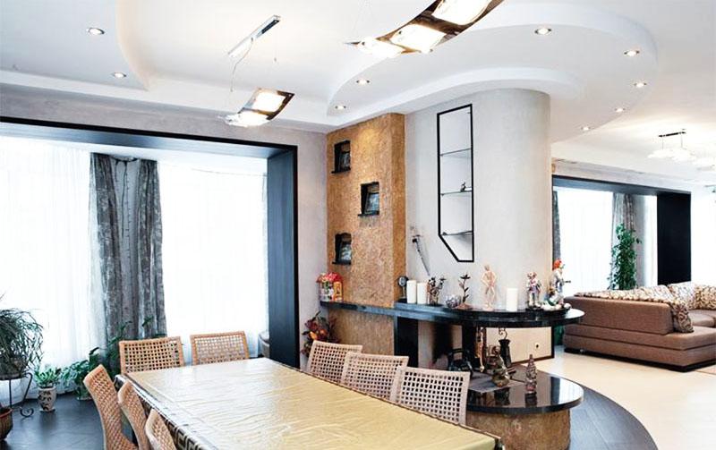 Сквозной камин в простенке разделяет зону отдыха от столовой