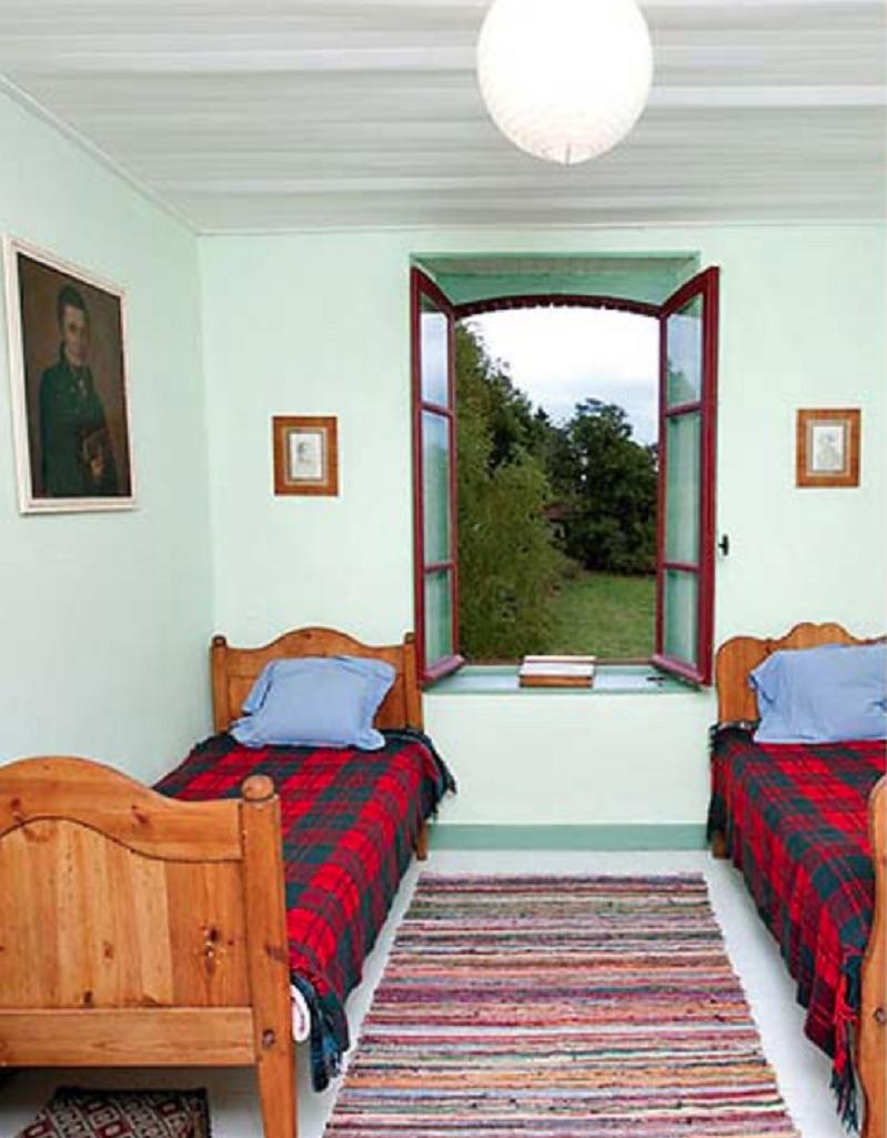 Стены гостевой спальни покрашены в нежный салатовый оттенок, на пол постелили дорожку ручной работы